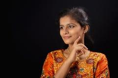 Portret szczęśliwa młoda Indiańska dziewczyna ono uśmiecha się na czarnym tle z ręką na podbródku zdjęcia stock