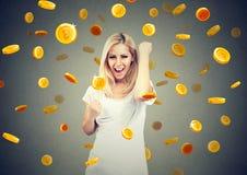 Portret szczęśliwa młoda kobieta świętuje pieniężnego sukces pod bitcoin deszczem fotografia stock