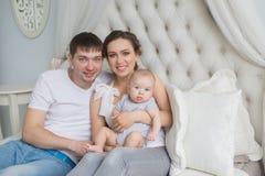 Portret szczęśliwa młoda rodzina z ich niemowlakiem Zdjęcia Stock