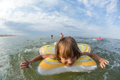 Portret, szczęśliwa mała dziewczynka pływa w morzu na nadmuchiwanym okręgu obrazy stock