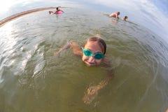 Portret, szczęśliwa mała dziewczynka pływa w morzu z szkłami obraz stock