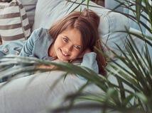 Portret szczęśliwa mała dziewczynka z długim brown włosy i przebijanie spoglądamy, kłamający na kanapie w domu samotnie Fotografia Royalty Free