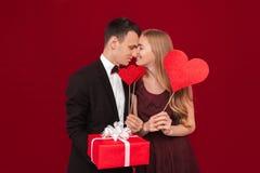 Portret szczęśliwa para, mężczyzny mienia papieru serca na czerwonym tle, kochanka dnia pojęcie obraz stock