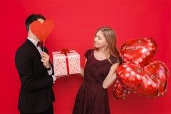 Portret szczęśliwa para, mężczyzny mienia papieru serca na czerwonym tle, kochanka dnia pojęcie obrazy royalty free