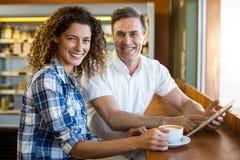 Portret szczęśliwa para używa cyfrową pastylkę w café fotografia royalty free