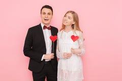 Portret szczęśliwa para w miłości trzyma papierowych serca na różowym tle, kochanka dnia pojęcie fotografia royalty free