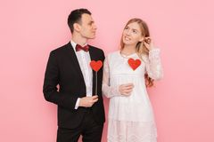 Portret szczęśliwa para w miłości trzyma papierowych serca na różowym tle, kochanka dnia pojęcie zdjęcia royalty free