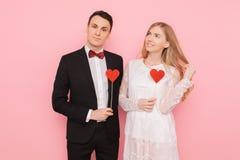 Portret szczęśliwa para w miłości trzyma papierowych serca na różowym tle, kochanka dnia pojęcie zdjęcie stock