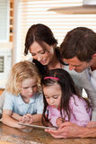 Portret szczęśliwa rodzina używa pastylka komputer wpólnie zdjęcia stock
