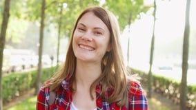 Portret szczęśliwa rozochocona młoda kobieta cieszy się naturę Stać w zieleń parku ono uśmiecha się przy kamerą zbiory