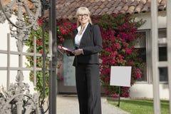 Portret szczęśliwa starsza agent nieruchomości pozycja przed domem Zdjęcia Royalty Free