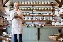 Portret szczęśliwa starsza handlowa pozycja z pikantność słojem w sklepie obrazy stock