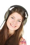 Portret szczęśliwa uśmiechnięta dziewczyna jest w słuchawkach Zdjęcia Stock