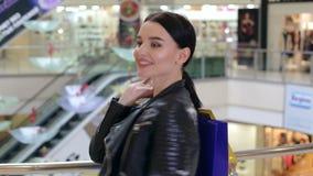 Portret szczęśliwa uśmiechnięta dziewczyna z papierowymi torbami w centrum handlowym blisko eskalatoru zbiory wideo