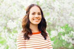 Portret szczęśliwa uśmiechnięta młoda kobieta nad białą wiosną kwitnie zdjęcia stock