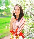 Portret szczęśliwa uśmiechnięta młoda kobieta nad wiosna kwiatami obraz stock