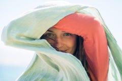 Portret szczęśliwa uśmiechnięta młoda kobieta z długie włosy Chuje cień z szalikiem i tworzy Fotografia Stock