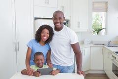Portret szczęśliwa uśmiechnięta rodzina używa cyfrową pastylkę Obraz Stock