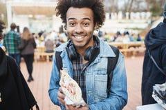 Portret szczęśliwa zadowolona afroamerykańska blogger mienia kanapka i ono uśmiecha się przy kamerą, excited kosztować je zdjęcie stock