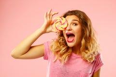 Portret szczęśliwego ładnego dziewczyny mienia słodki cukierek nad różowymi półdupkami Zdjęcia Royalty Free