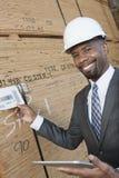 Portret szczęśliwego amerykanina afrykańskiego pochodzenia męski kontrahent używa pastylka peceta podczas gdy sprawdzać drewniane  Zdjęcia Stock
