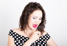 Portret szczęśliwego pięknego młodej kobiety oblizania słodki cukierek i wyrażać różne emocje kierowa ładna kobieta obraz stock