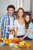 Portret szczęśliwego rodzinnego narządzania owocowy sok Fotografia Stock