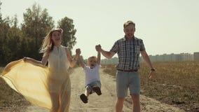 Portret szczęśliwi kochający rodzice trzyma ich syna jest rękami i udźwigiem up on zbiory