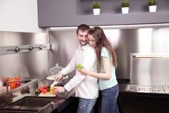 Portret szczęśliwi potomstwa dobiera się kucharstwo w kuchni wpólnie Obraz Stock
