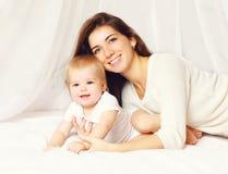 Portret szczęśliwi uśmiechnięci potomstwa macierzyści i śliczny dziecko na łóżku Zdjęcia Stock