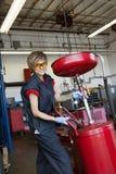 Portret szczęśliwy żeński mechanik pracuje na spawalniczym wyposażeniu w garażu Fotografia Royalty Free