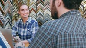 Portret szczęśliwy żeński sprzedawca bierze rozkaz na obrazek ramie od klienta, pisze puszek notatkach w laptopie Zdjęcia Stock