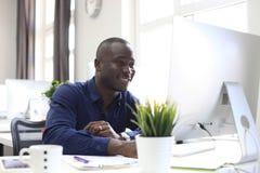 Portret szczęśliwy amerykanina afrykańskiego pochodzenia przedsiębiorca wystawia komputer w biurze obrazy royalty free