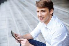 Portret szczęśliwy biznesmen używa pastylkę outdoors zdjęcie stock