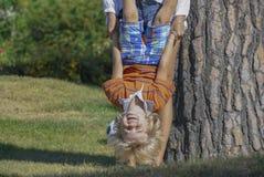 Portret szczęśliwy dzieciaka bawić się do góry nogami Zdjęcia Stock