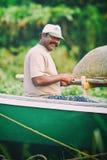 Portret szczęśliwy Indiański rybak rozplątuje sieci rybackie i sprzęt podczas gdy siedzący w łodzi, Kerala India rybołówstwa zato Fotografia Stock