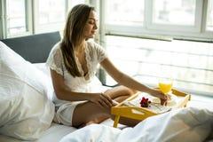 Portret szczęśliwy kobiety łasowania śniadanie w łóżku obrazy stock