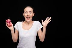 Portret szczęśliwy kobiety mienia prezent w ręce i patrzeć kamera na czerni Obraz Stock
