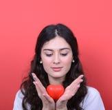 Portret szczęśliwy kobiety mienia serce w rękach przeciw czerwonemu backg obraz royalty free