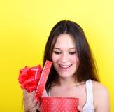Portret szczęśliwy kobiety otwarcia prezenta pudełko przeciw żółtemu backgrou obrazy stock