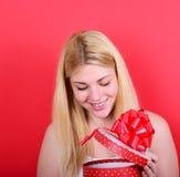 Portret szczęśliwy kobiety otwarcia prezenta pudełko przeciw czerwonemu tłu obraz royalty free