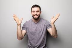 Portret szczęśliwy mężczyzna wzrasta up ręki i pomyślnego osiągnięcie cele na popielatym Fotografia Stock
