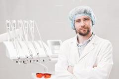 Portret szczęśliwy męski dentysta jest ubranym lab żakiet podczas gdy siedzący w klinice Zdjęcia Royalty Free