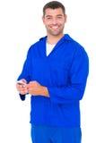 Portret szczęśliwy męski mechanik używa telefon komórkowego zdjęcia stock