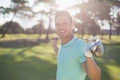 Portret szczęśliwy młodego człowieka przewożenia kij golfowy Zdjęcie Stock