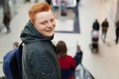 Portret szczęśliwy młody atrakcyjny modniś jest ubranym kurtkę i trzyma plecaka z czerwony włosiany trwanie w zakupy centrum hand Fotografia Stock