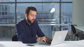 Portret szczęśliwy młody biznesmen z laptopu obsiadaniem biurkiem w biurze zdjęcie wideo