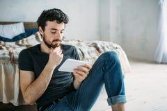 Portret szczęśliwy młody człowiek relaksuje TV przedstawienie na pastylka komputerze i ogląda fotografia royalty free