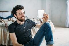Portret szczęśliwy młody człowiek relaksuje TV przedstawienie na pastylka komputerze i ogląda zdjęcia stock