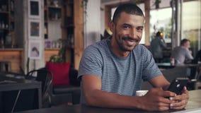 Portret szczęśliwy młody człowiek używa mądrze telefon w kawiarni zbiory